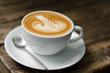 Foamy latte coffee on dark grained wood table form above - 70578488