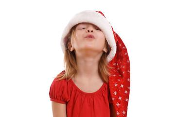 kleines Mädchen mit Kussmund und Weihnachtsmütze