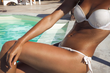 Tanned woman body by the pool.