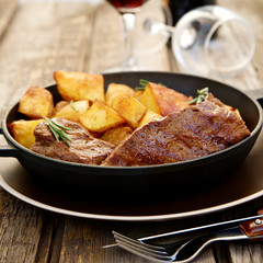 Beef steak in a pan with baked potatoes and red wine