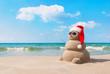 Christmas snowman in santa hat at sandy beach