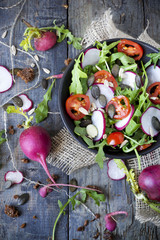 rocket salad on bowl with radish, tomatoes and seed