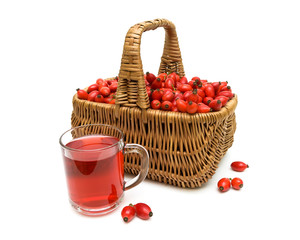 basket with berries of wild rose and a drink in a glass mug on a
