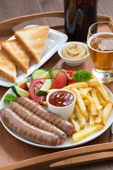 lunch with grilled sausages with French fries, vegetables, beer