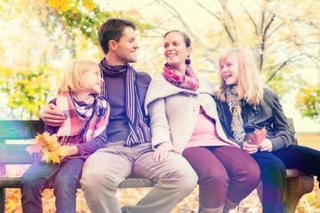 Glückliche Familie sitzt auf Parkbank im Herbst
