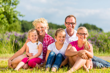 Familie spaziert vor Haus und Eigenheim