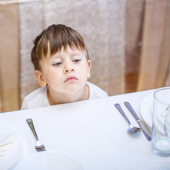 3 years old boy at an empty table