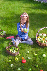 Happy little girl with autumn harvest of tomato in baskets