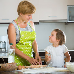 Happy child with woman making meat dumplings