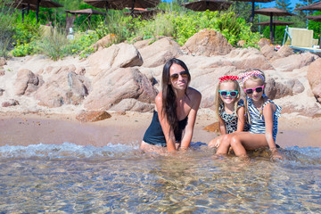 Young mother and two her kids at exotic beach on sunny day