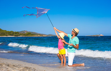 Happy father and little girl playing with kite on summer beach