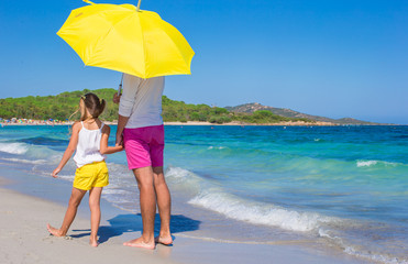 Back view of father and daughter at white beach with yellow