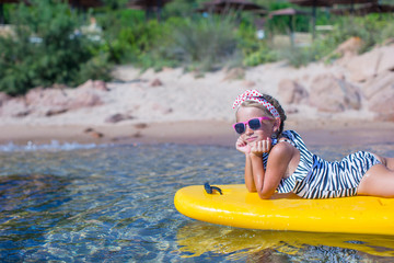 Little girl enjoying swimming in yellow kayak in the clear