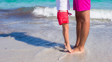 Little girl standing on her father's feet at the white sandy