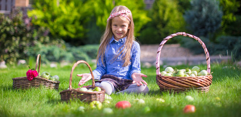 Adorable little girl with autumn harvest of tomato in baskets
