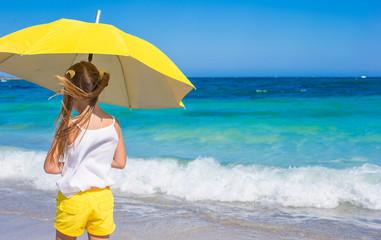 Little girl with big yellow umbrella walking on tropical beach