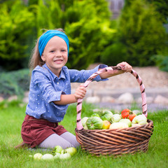 Portrait of little girl with autumn harvest of tomato in baskets
