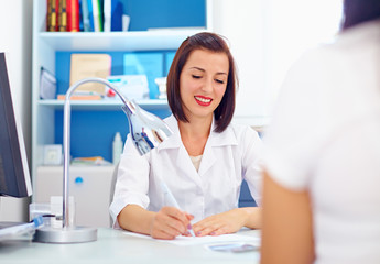 female doctor writes the prescriptions to patient