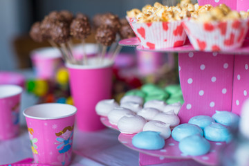 Sweet colored meringues, popcorn, custard cakes and cake pops on