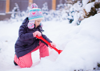 Little adorable girl play with snow shoveling on winter day