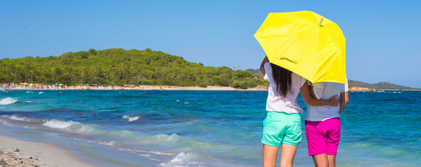Back view of romantic couple at white beach with yellow umbrella