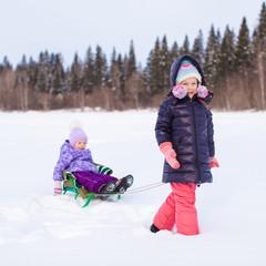 Adorable little happy girl sledding her cute sister