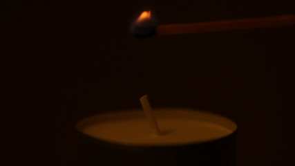 Lighting a candle with a match to get a romantic candlelight