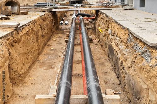 Neue und alte Fernwärmerohre in einer Baugrube - 70589415