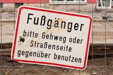 Ein schmutziges Schild an einem Bauzaun