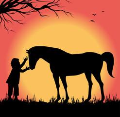 silhouette di bambino che accarezza un cavallo