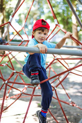 Little boy in cap climb on jungle gym