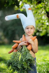 funny boy in bunny costume and an armful of fresh carrots