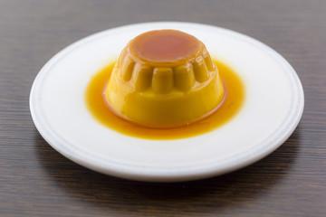 Creme caramel vanilla custard dessert or flan on white dish