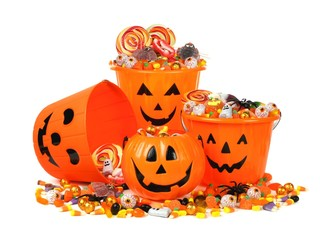 Group of Halloween Jack o Lantern pails with pile of candy