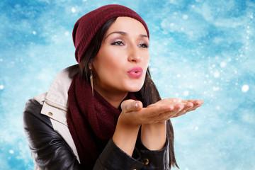 schöne Frau pustet Schnee