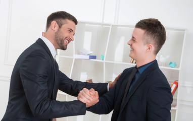 Waist-up portrait of two handsome businessmen in suits handshaki