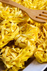 Raw tagliatelle with wooden fork, portrait view