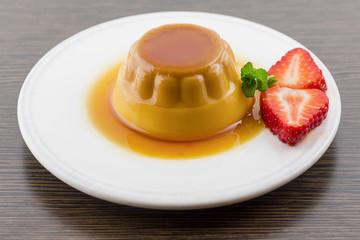 Creme caramel vanilla custard dessert or flan on white dish with