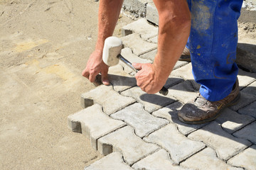 Worker laying interlocking pavers