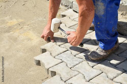 Leinwanddruck Bild Worker laying interlocking pavers