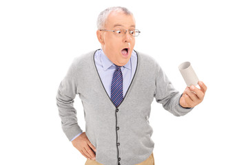 Baffled senior holding an empty toilet paper roll