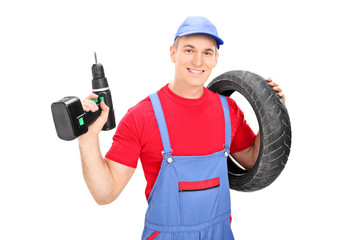 Male mechanic holding a tire and a drill