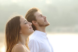 Couple of man and woman breathing deep fresh air - 70594042