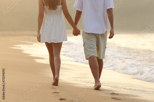 Couple taking a walk holding hands on the beach - 70594093