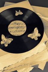 Vinyl record with old paper and butterflies, close-up