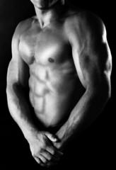 Sexy muscular man on dark background in shades of grey