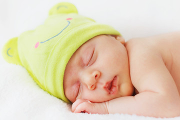Close up happy baby girl new born sleeping in green hat