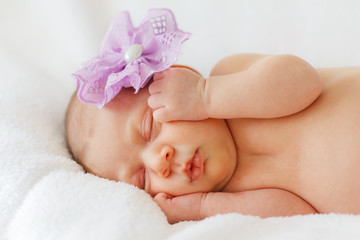 Portrait happy baby girl new born sleeping with purple flower