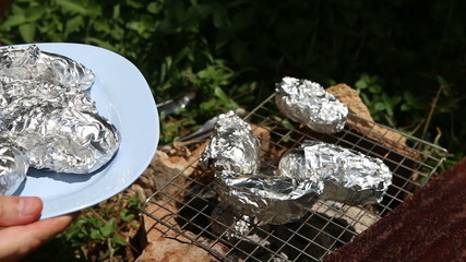 baked potatoes on the grill in foil at the stake
