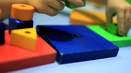 Toddler Child Plays with Colorful Blocks and Shapes